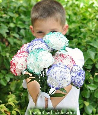 young boy holding up a bouquet of paper flowers