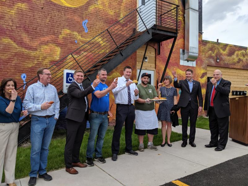Syracuse Mayor Walsh and Home HeadQuarters CEO Kerry Quaglia among others, help celebrate the Lasher Hardware restoration with an empanada and taco toast compliments of Ponchito's, a local taqueria that is moving into the first level of the building.