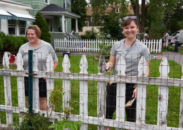 Employees from Pathfinder Bank help paint a fence during Home HeadQuarters' 2018 Block Blitz
