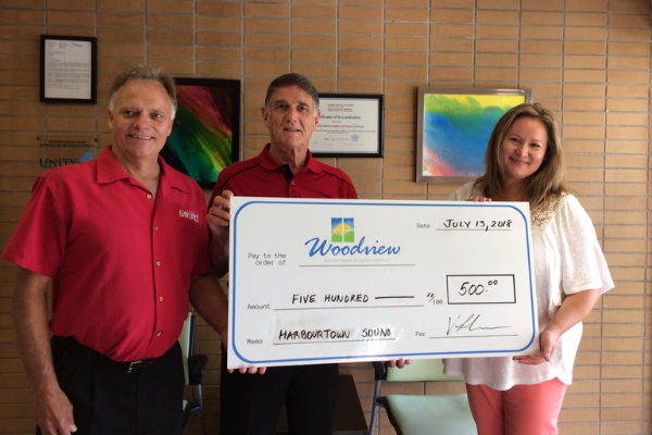 Vic Linka and Jim Boyd of Harbourtown Sound, present a donation cheque to Michelle Bake-Murphy of Woodview