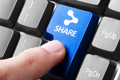 Sharing file. gesture of finger pressing share button on a computer keyboard