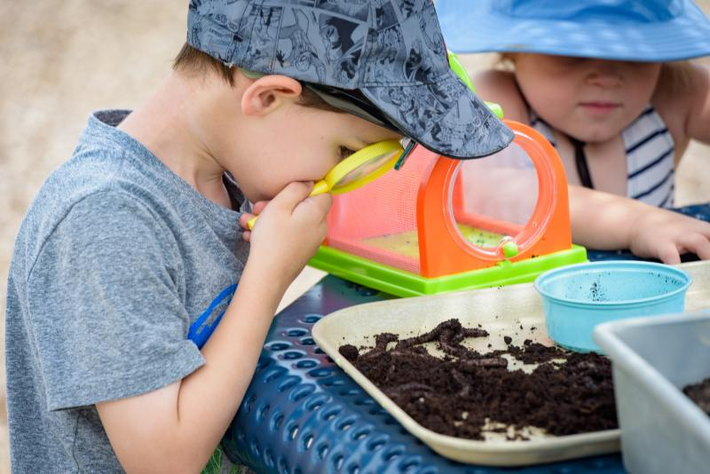 boy examining worms with magnifying glass