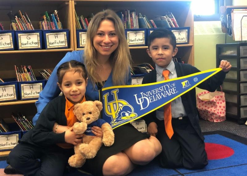 UD alumna with UD pennant in her classroom
