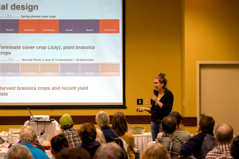 Carmen Black, of Sundog Farm near Solon, holds a microphone and speaks about on-farm research to farmers attending Practical Farmers of Iowa's 2018 Cooperators' Meeting.