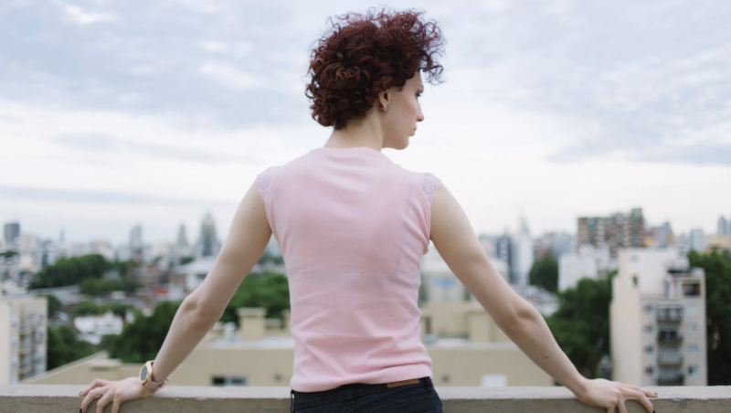 Young woman standing on rooftop looking out at view