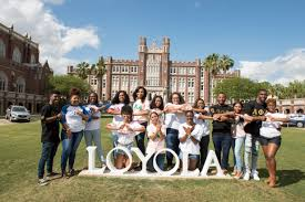 Image of students gathered around a Loyola sign on the Loyola New Orleans campus