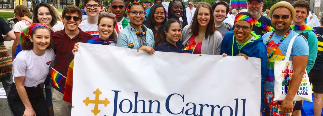 A group of 16 people holds a John Carroll University banner at the Pride in the CLE march