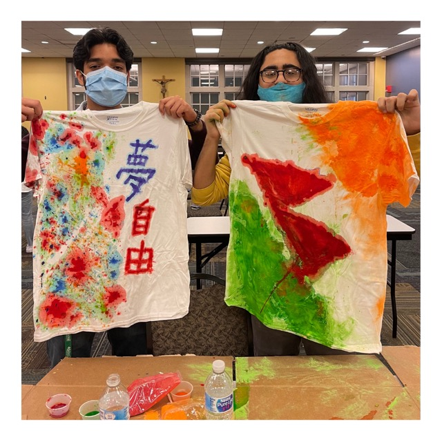 photo of two students holding up decorated tshirts