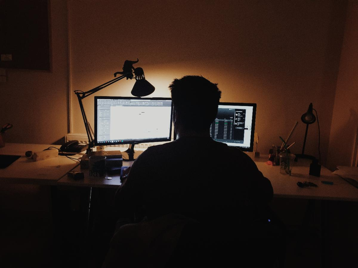 image of someone working at a computer in the dark