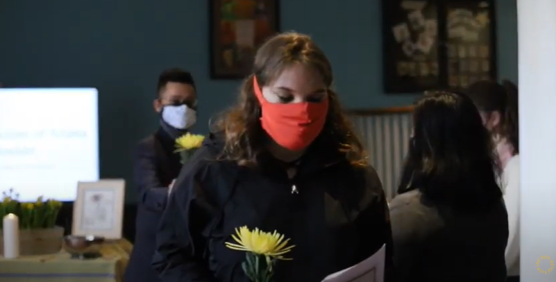 photo from the March 26 vigil - students in masks holding flowers
