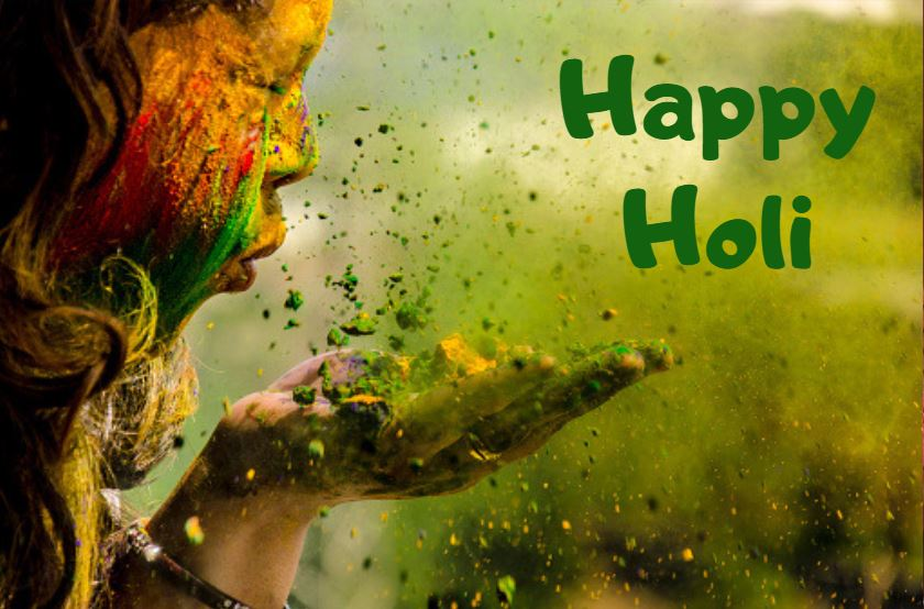 image of a child covered in brightly colored powder and the words Happy Holi