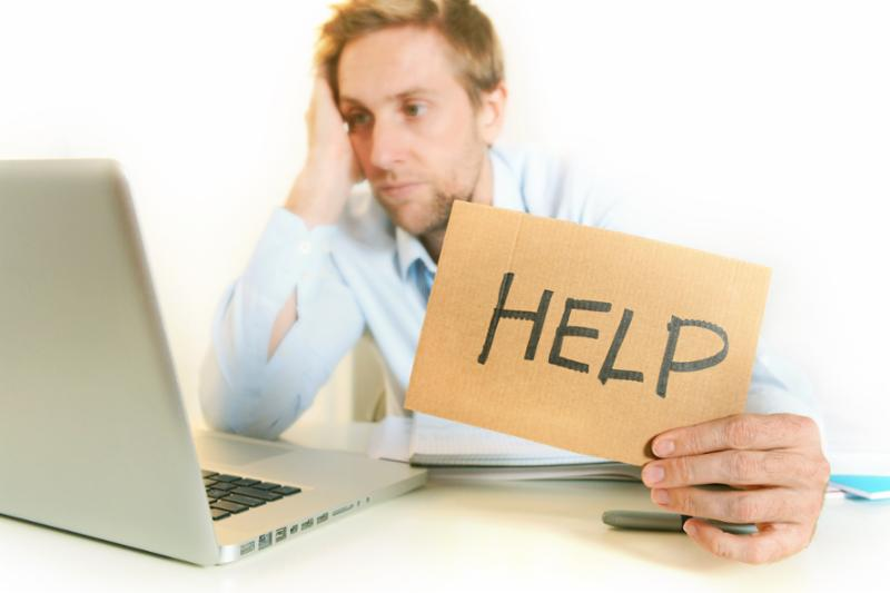 Man sitting at computer holding a sign reading HELP