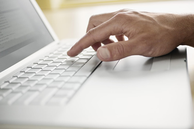 image of a hand typing on a computer keyboard
