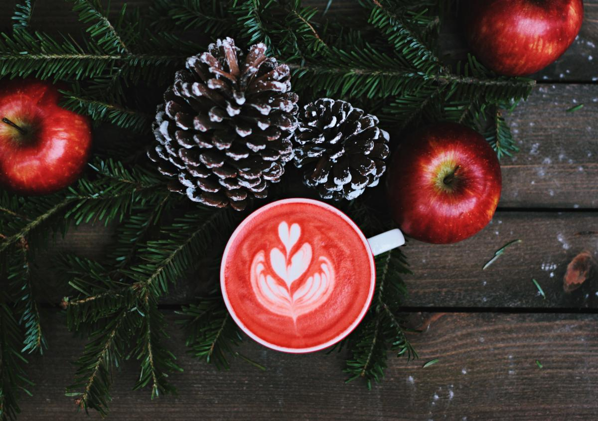 image of wintry pinecones apples and a warm red holiday latte