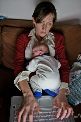 Photo of tired mother working at a laptop with a baby asleep on her chest