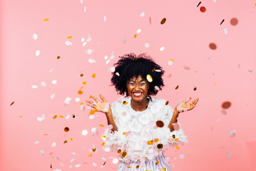 Celebrating happiness_ young woman with big smile throwing confetti