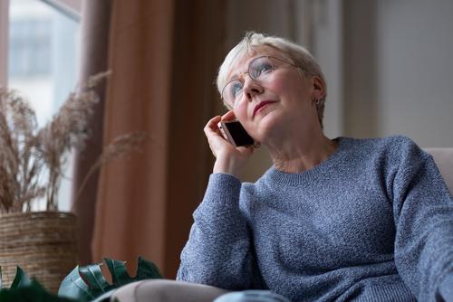 Senior woman talking on mobile phone sitting at sofa at home