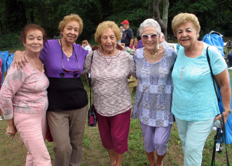 Five ladies, standing with arms around each other posing for camera and smiling.