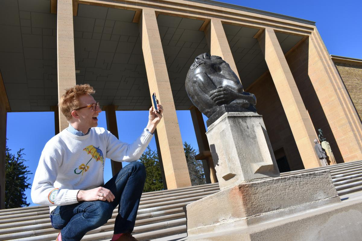 Photograph of Cranbrook Center for Collections and Research Curatorial Associate Kevin Adkisson giving a live tour on social media on the steps of Cranbrook Art Museum, spring 2019.