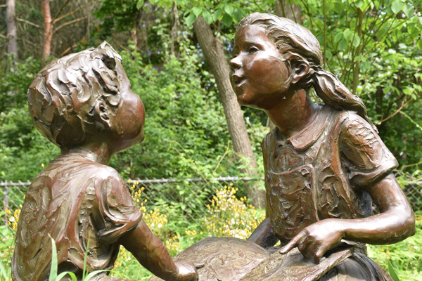 Photograph of a sculpture of a boy and girl reading at Cranbrook Schools.