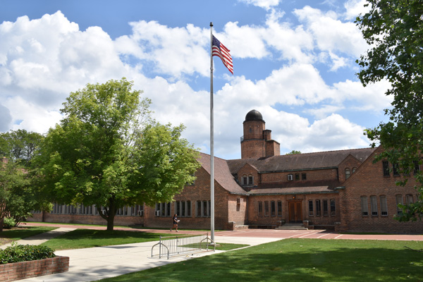 Photo of a student walking by an American flag at Cranbrook Schools, July 2019.