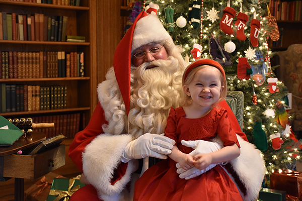 Photograph of a girl in a red dress with Santa during Holiday Splendor 2018 in the Cranbrook House Library.