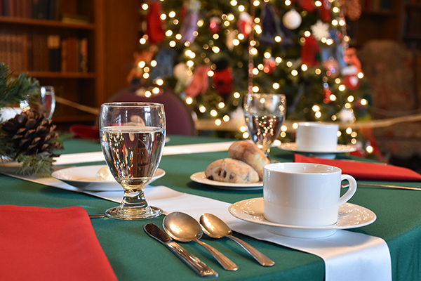 Photograph of a table setting with a holiday tree in the background in the Cranbrook House Library.