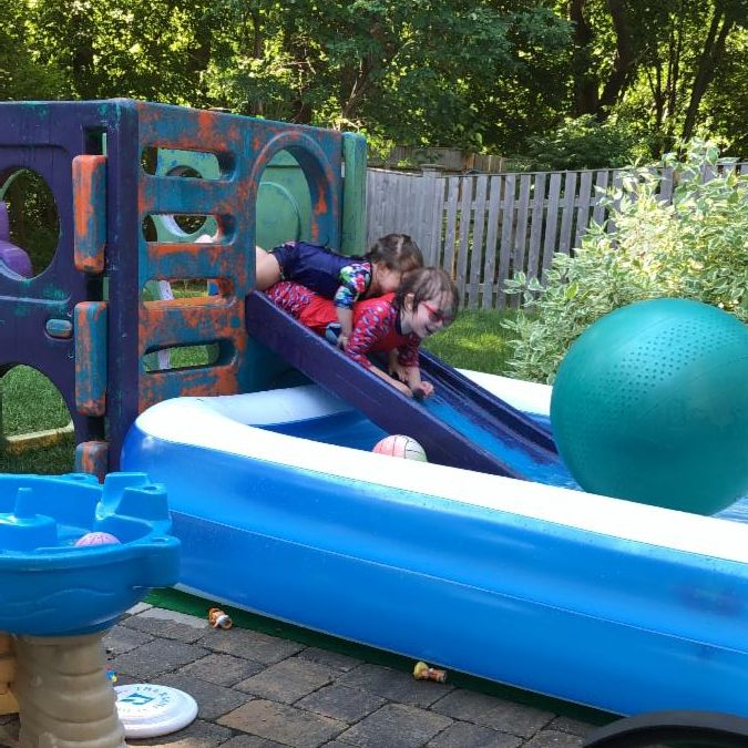 Two kids in bathing suits playing on a slide and a backyard pool.