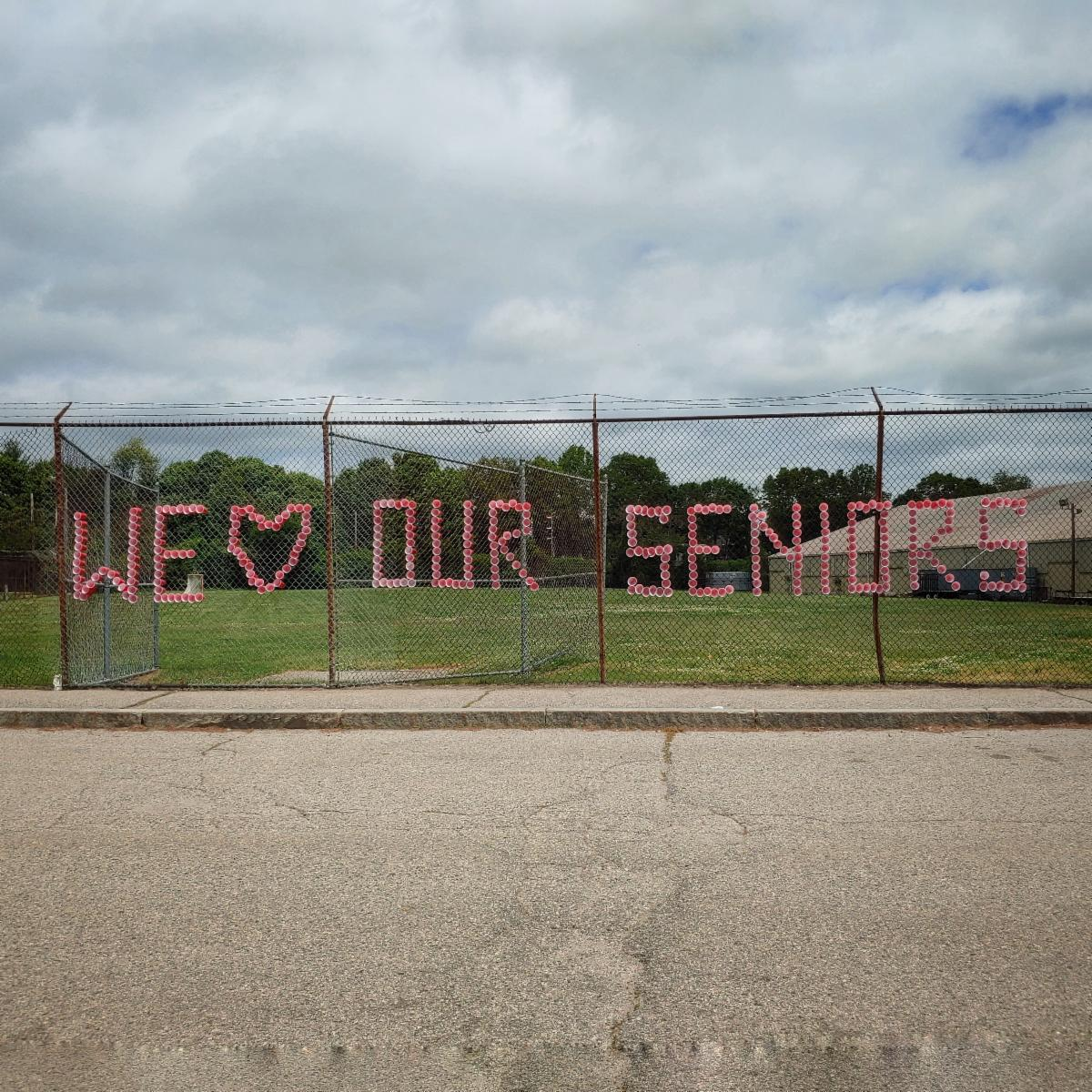 A photo of a chainlink fence with We Heart Our Seniors spelled out in red plastic cups pushed through holes in the fence.