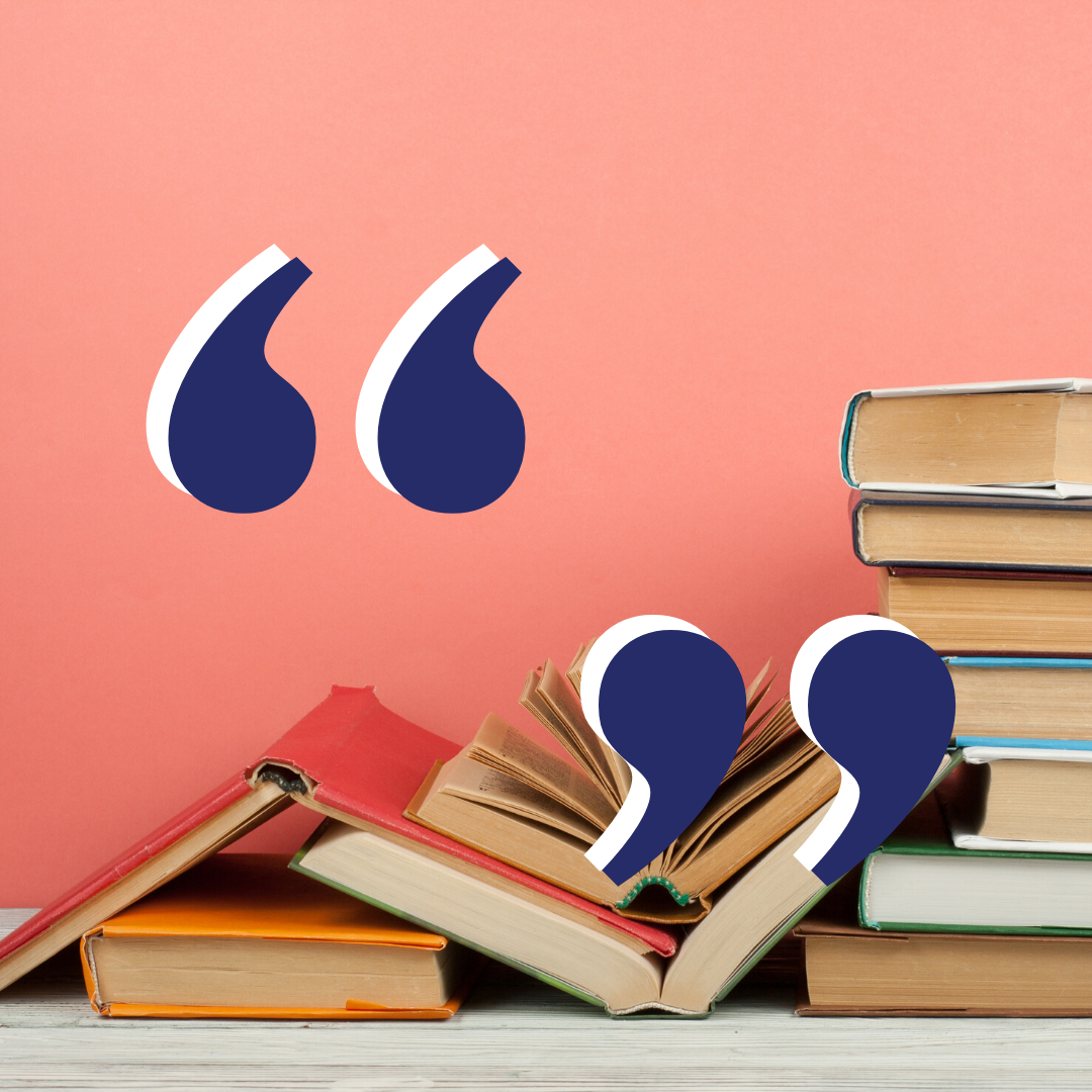 Quotation marks over stacks of books in front of a pink wall.