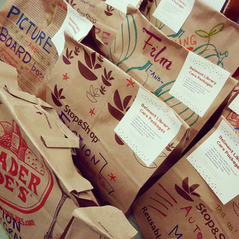 "Brown paper bags with genre labels in colorful marker and notes saying ""Belmont Library Care Packages"""