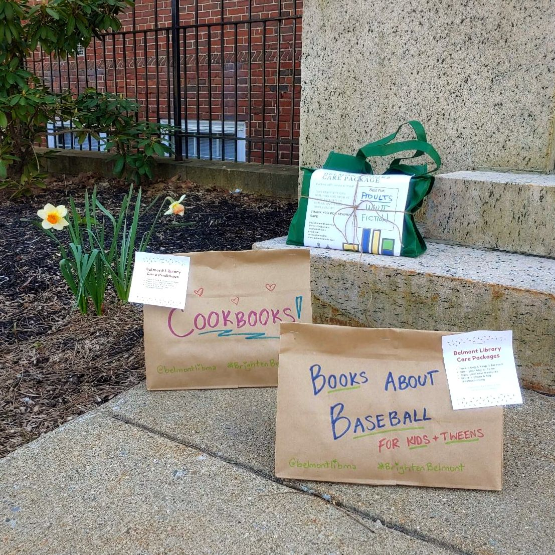 3 bags of books on stone steps with daffodils in the background.