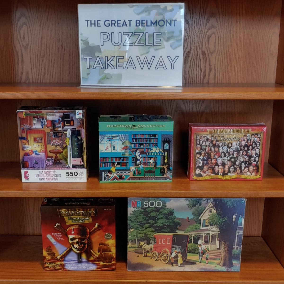 A bookcase with puzzles and a sign saying The Great Belmont Puzzle Takeaway