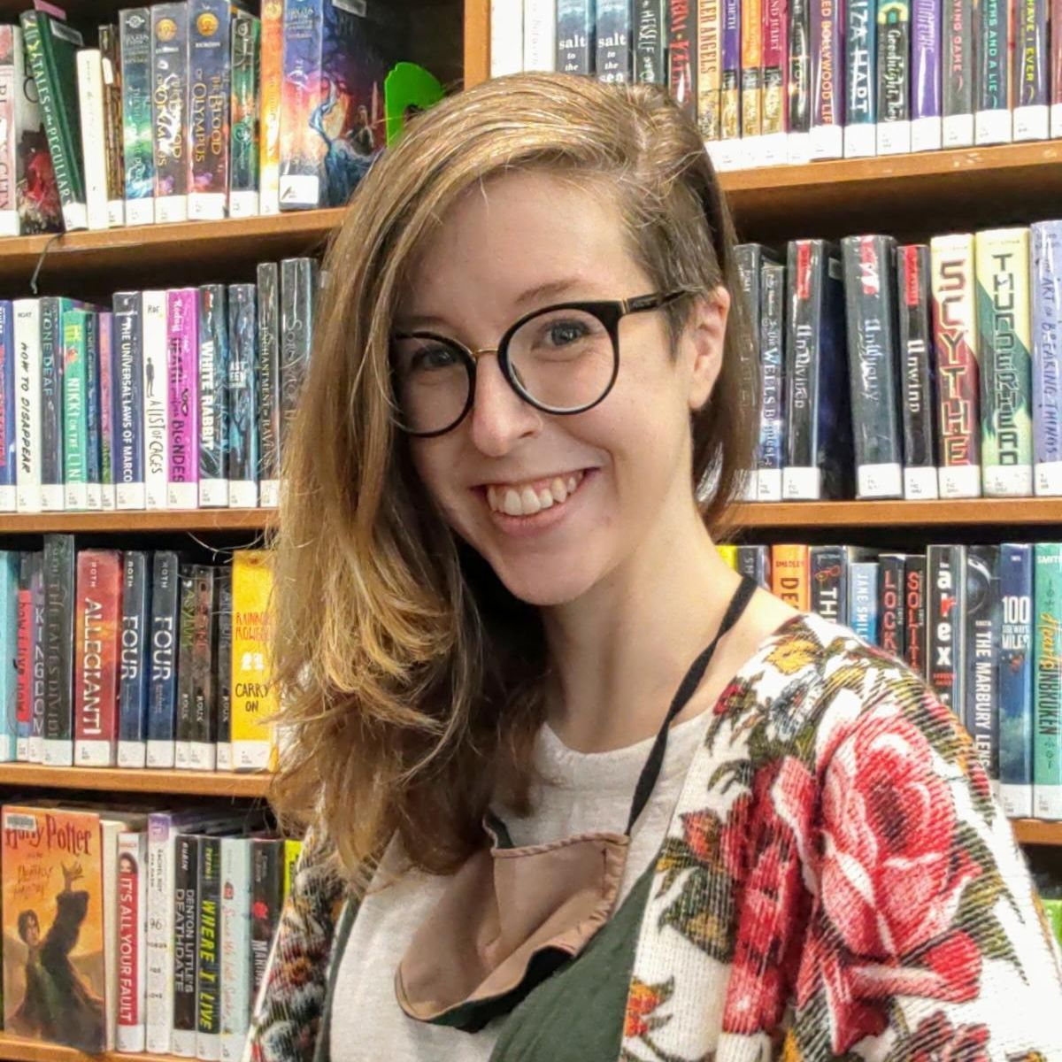Librarian Hannah Lee standing in front of shelves of teen fiction.