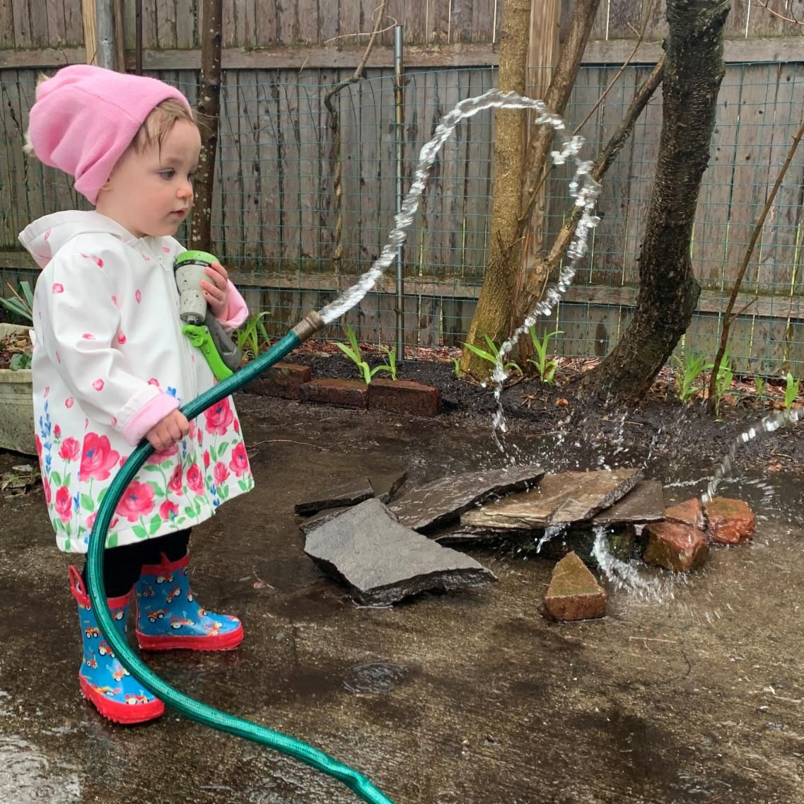 A girl in a raincoat, boots, and pink hat watering rocks with a hose.