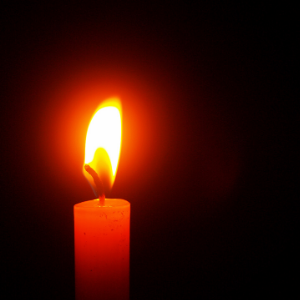 A lit candle against a black background.