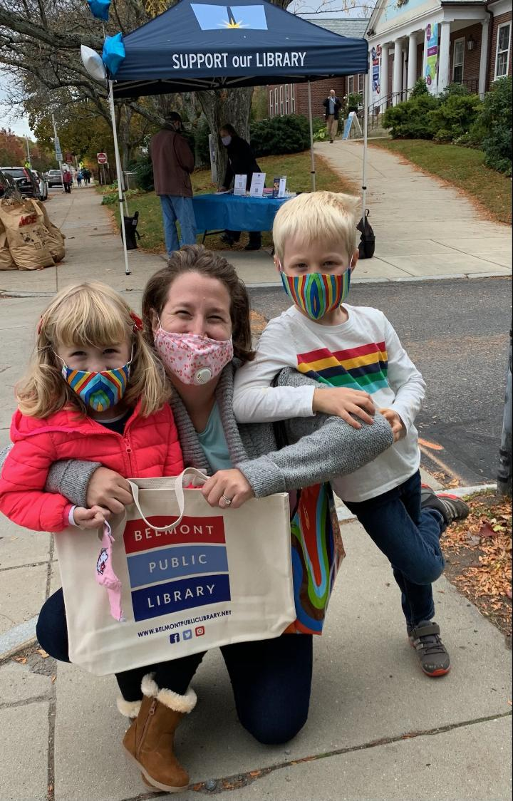 A parent and two children outside the Belmont Public Library are wearing colorful face masks and proudly holding a canvas bag with the library's logo. They are in front of a blue tent that says Support Our Library.