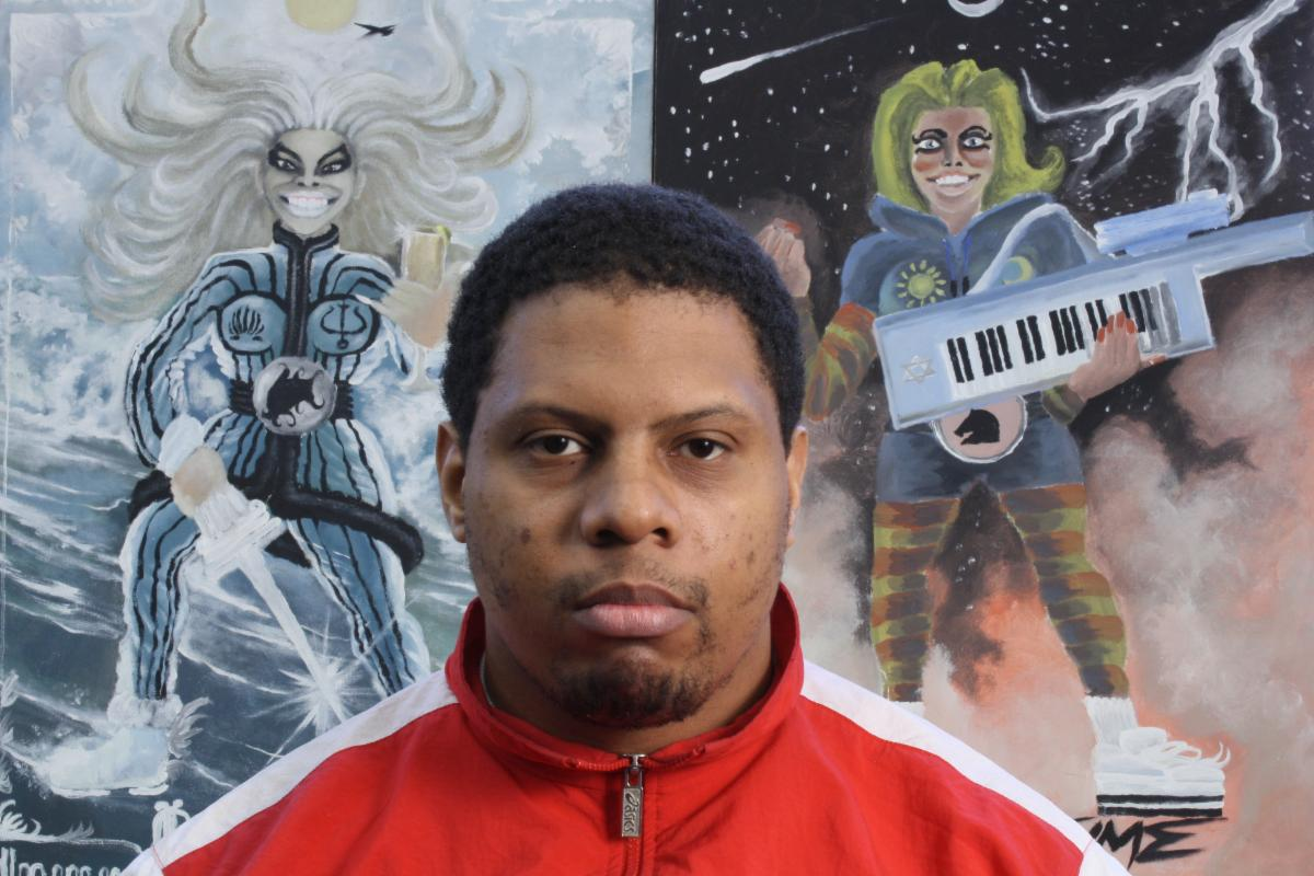 Headshot of Knicoma Frederick in front of 2 pieces of art