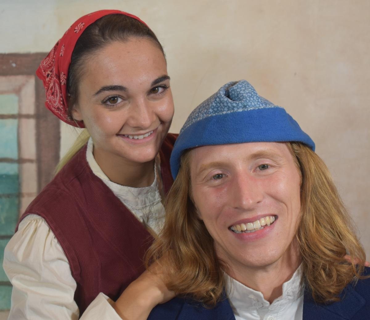 Headshot of male and female actors dressed in costume with the woman leaning on the man's shoulder in front of a beige wall with a window painted on it that is part of the show's set