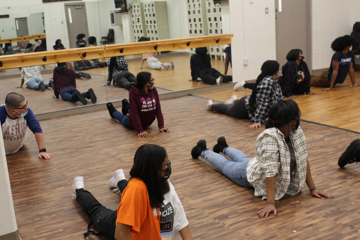 Youth stretching on a wood-patterned floor in front of a mirror in a dance studio