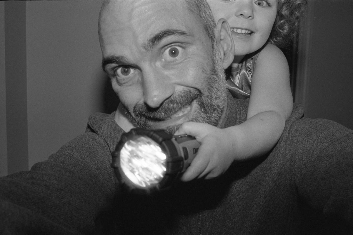 Selfie headshot of Jason Jellick with small child holding a flashlight on his back