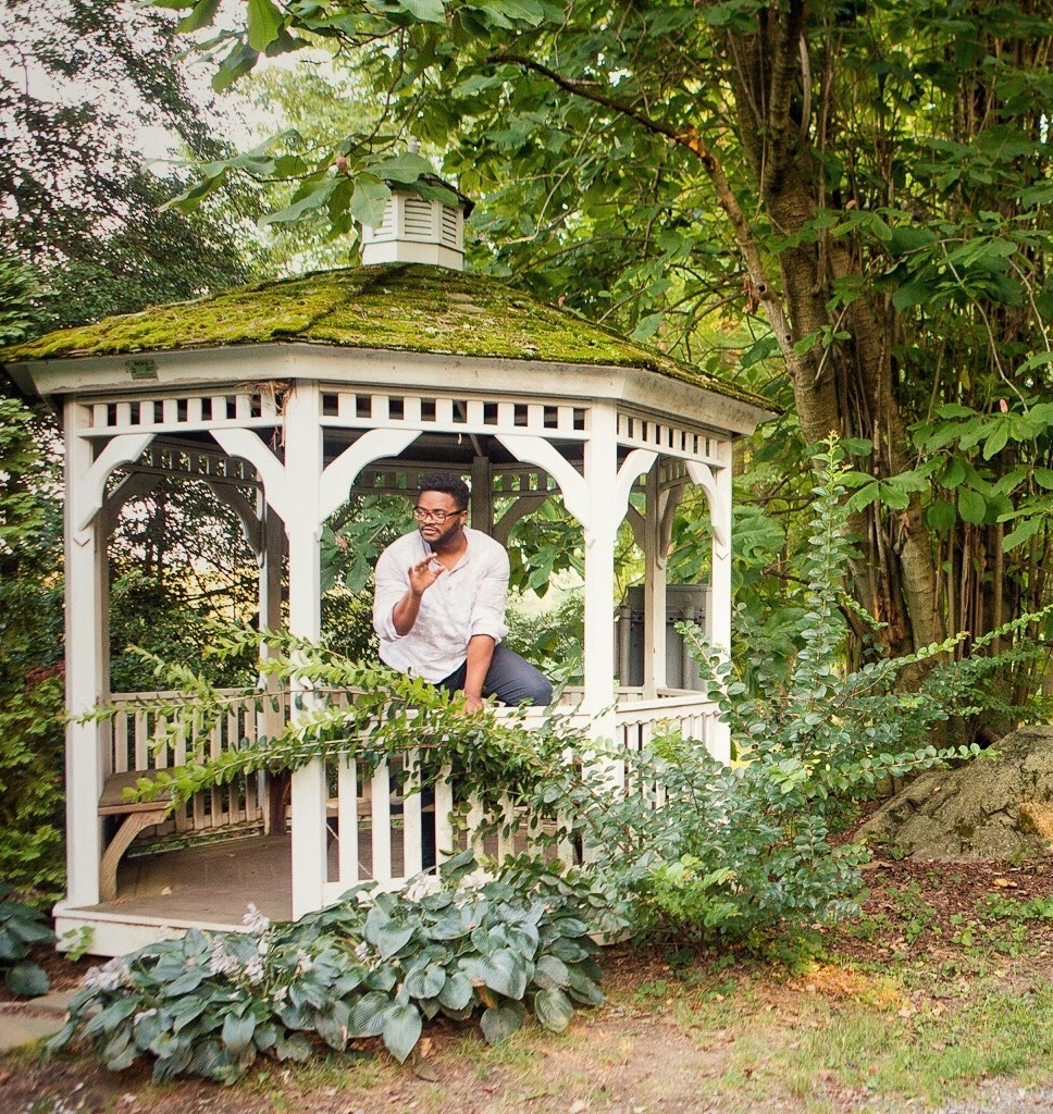 Male actor in costume standing in a white wooden gazebo with a moss covered roof surrounded by trees and greenery in the foreground and background