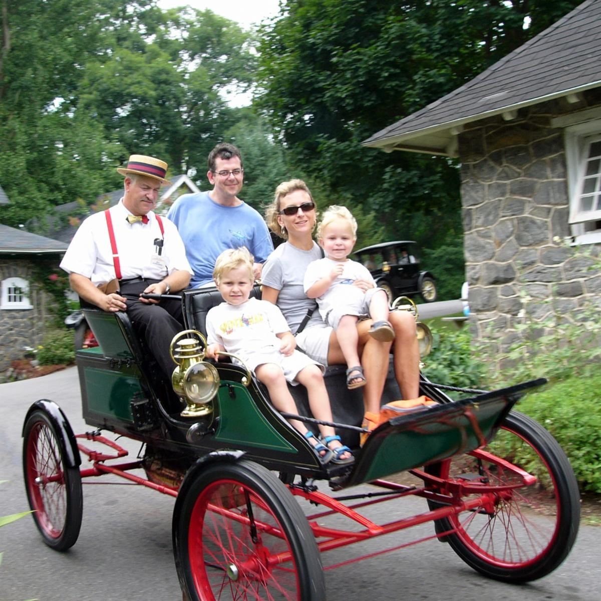 Family unit of 4 riding in a green and red antique car with a man in period clothes driving the car