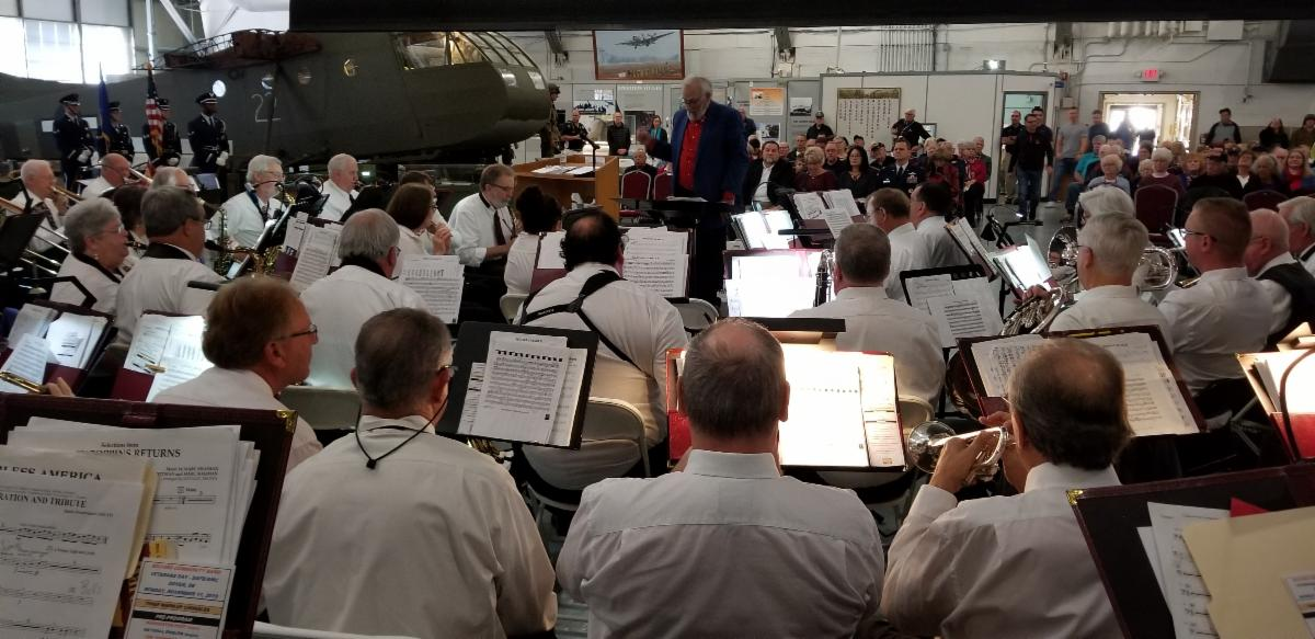 The backs of musicians with their stands and sheet music in the foreground looking at the director the audience and a helicopter in the background with the concert taking place in the Air Mobility Museum