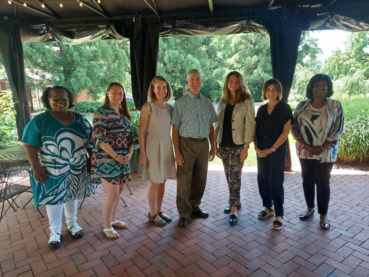 June 2021 Delaware Division of the Arts staff group photo of seven people standing outside under a covered porch with greenery in the background