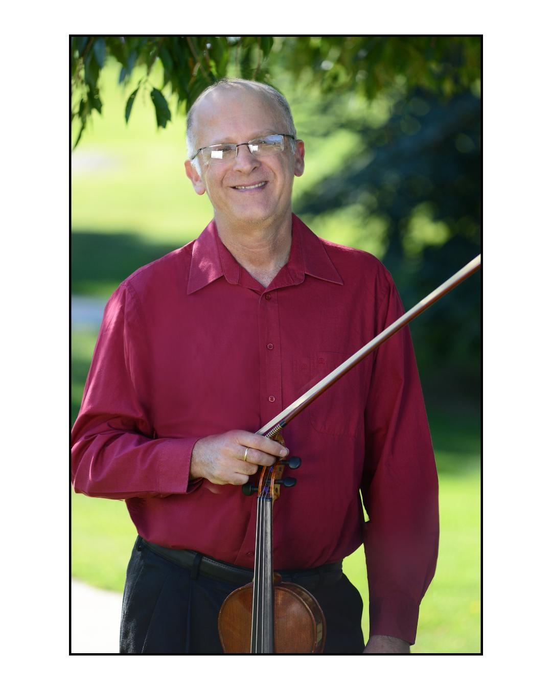 three quarter length portrait of Eliezer Gutman holding his violin outside