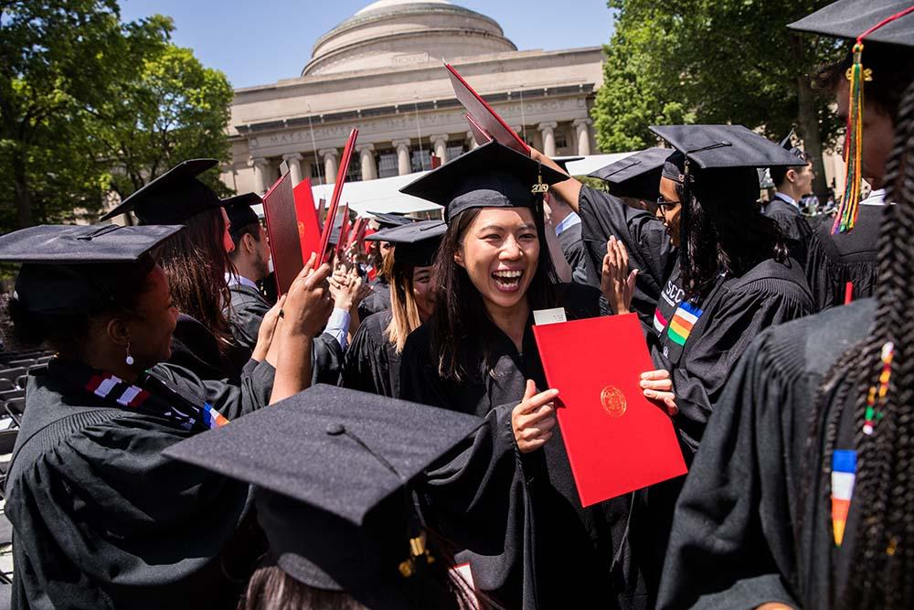 Happy graduate holds up her MIT diploma at Commencement; Photo: Jake Belcher