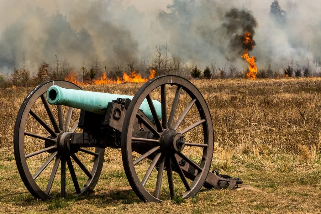 A line of grassland fire along the horizon behind a civil war canon