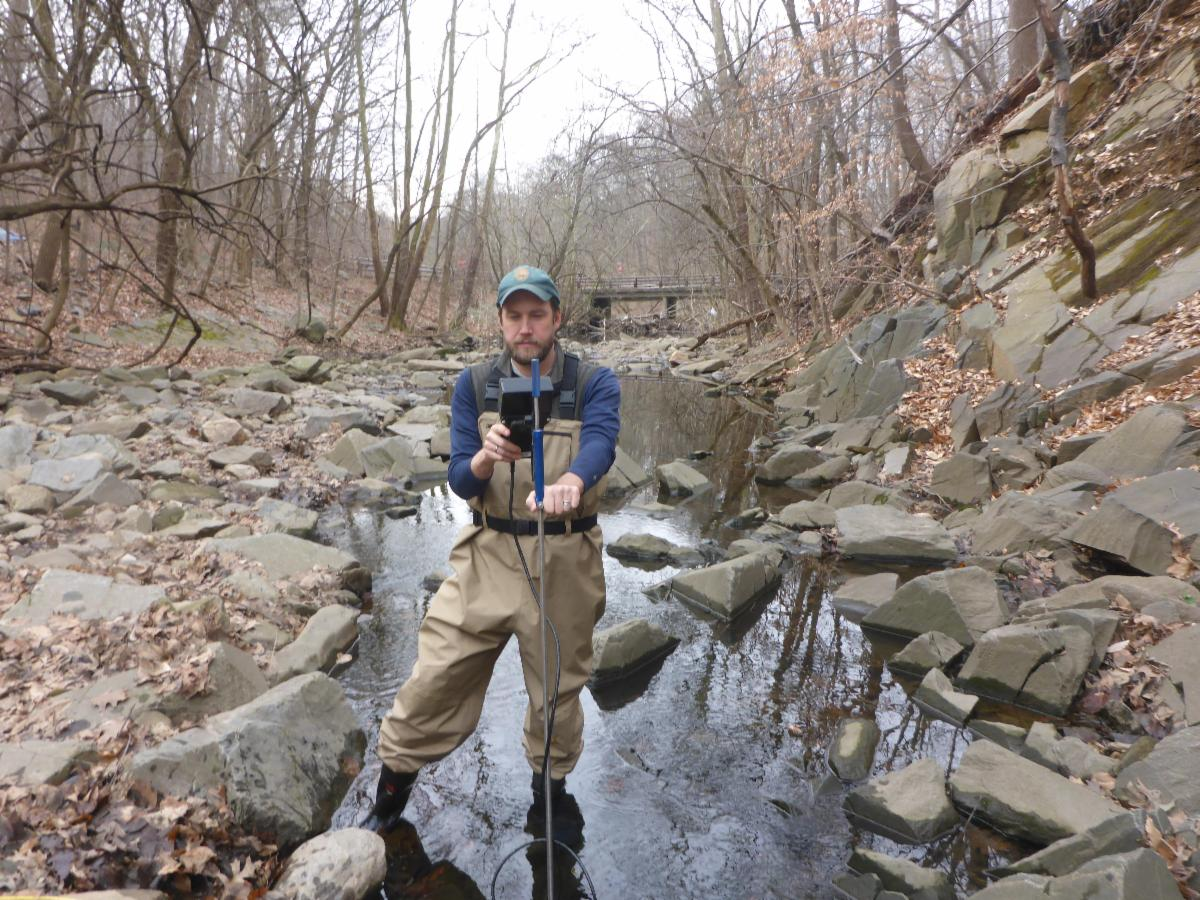 Man in waders stands in a shallow forest stream in winter