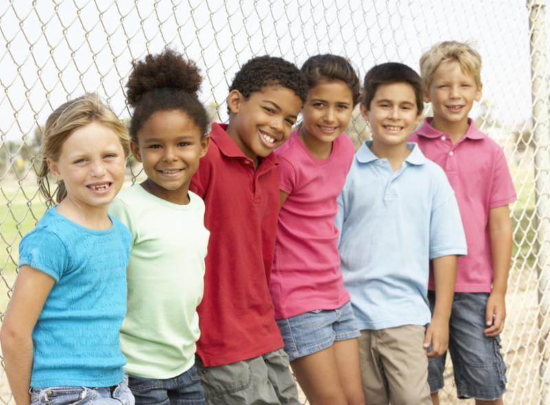 children_smiling_by_fence.jpg